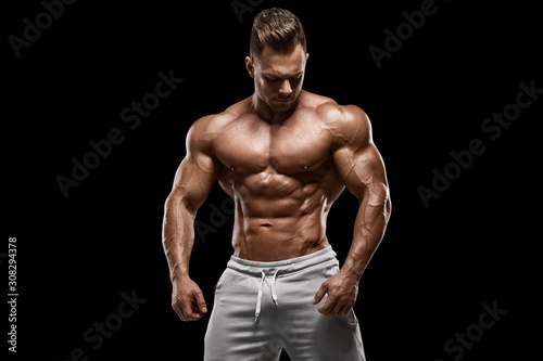 Obraz Muscular man showing muscles isolated on the black background. Strong male naked torso abs - fototapety do salonu