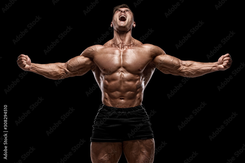 Fototapeta Muscular man showing muscles isolated on the black background. Strong male naked torso abs
