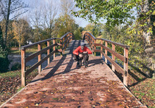 Young Man Hugging His Dog At The End Of A Wooden Bridge On A Cold Autumn Morning.