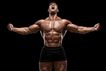 Muscular man showing muscles isolated on the black background. Strong male na...