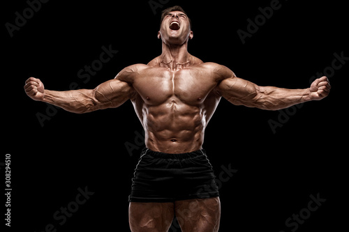 Fototapeta Muscular man showing muscles isolated on the black background. Strong male naked torso abs obraz