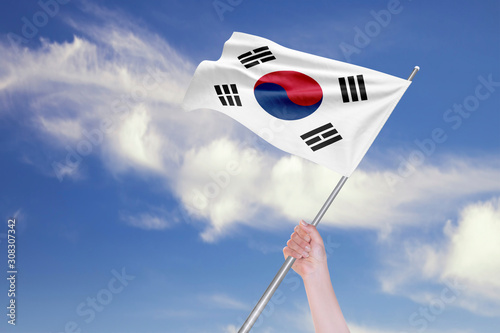 Fototapeta  Female Hand is Waving South Korean Flag Against Blue Sky with Clouds
