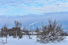 City Landscape. Trees Covered With Snow. Chimney With Smoke In Residents Area. Ecological Concept Image. Factory Pollutes The Atmosphere In During Winter Time By Harmful Emissions.