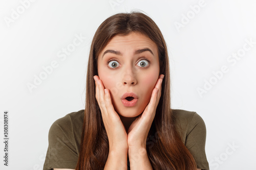 Photo Close-up portrait of surprised beautiful girl holding her head in amazement and open-mouthed
