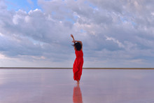A Young Woman In A Long Red Dress Walks On The Lake Before The Coming Storm