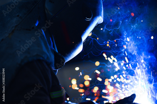 Photo technician working with electric arc welding