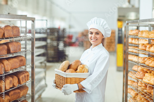 Fototapeta A baker woman holding a basket of baked in her hands at the bakery obraz