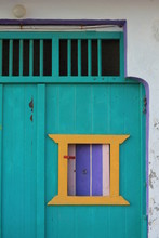 Colorful Green, Yellow, And Purple Window On A White Building In Milos, Greece
