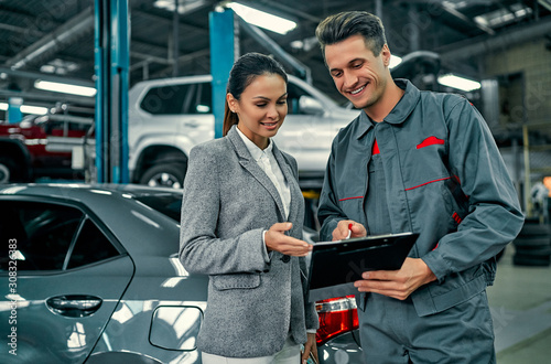 Fotomural Beautiful businesswoman and auto service mechanic are discussing the work and signing documents
