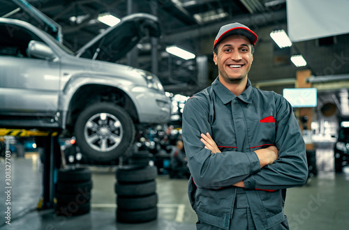 obraz dibond Handsome auto service mechanic in uniform is standing on the background of car with open hood, smiling and looking at camera. Car repair and maintenance.
