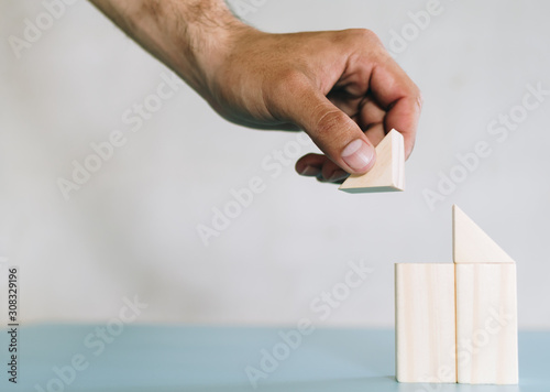 Fotografie, Obraz part of human hand while building house from natural color wooden block