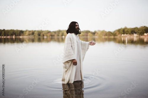 Fotografia Jesus Christ walking in the water with his hand up