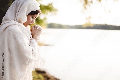 Fototapeta Shallow focus shot of a female wearing s biblical gown and praying while her eye
