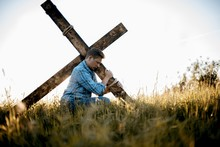 Shallow Focus Shot Of A Male Carrying A Handmade Cross