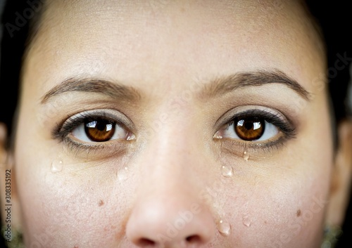 Fotomural Closeup shot of an emotional female crying while looking at the camera - concept