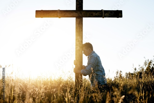 Fotografija Male with his head leaned against a hand made wooden cross while praying
