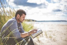 Shallow Focus Shot Of A Male Sitting On The Beach Shore While Reading The Bible