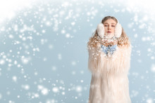 Happy Young Woman In Winter Clothes Blowing Snow On Color Background