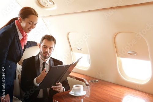 Air hostess showing menu to businessman on board the modern private airplane Wallpaper Mural