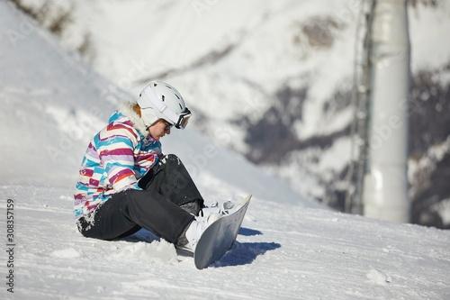 obraz PCV Snowboarder adjusting binding on her equipment