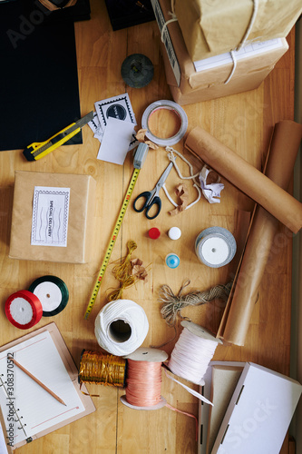 Obraz Decorative paper, various strings and ropes for wrapping presents on table of creative person - fototapety do salonu