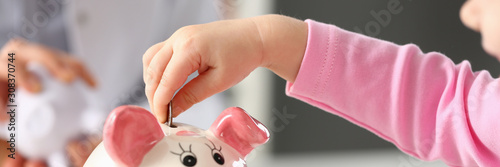 Hand of little girl putting coins in funny piggy bank pin slot Fototapete