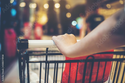 Cuadros en Lienzo  Asian woman's hand with supermarket, trolley and many objects that are blurred background