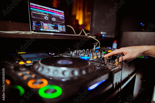 Dj mixing outdoor at beach party festival with crowd of people in background - Summer nightlife view of disco club outside - Soft focus on hand - Fun ,youth,entertainment and fest concept - 308381503