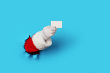 Santa Claus Holding A Blank White Card Isolated Over Light Blue