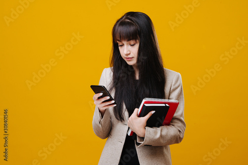 Young tired business woman in a grey suit checking her phone over yellow Fototapeta