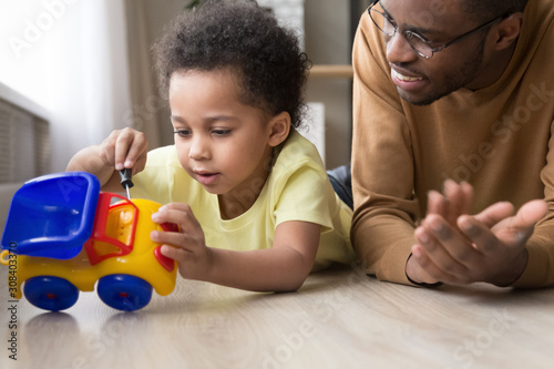 Canvastavla  Smart little kid fix toy car playing with dad