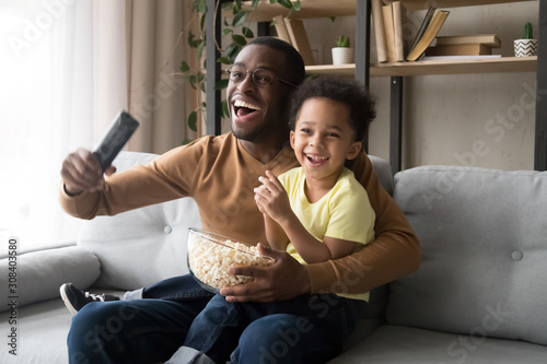 Fotografie, Tablou  Excited black dad and son cheering watching match on TV