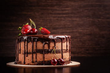 Čokoladna torta s bobičastim voćem, jagodama i trešnjama. kolač na tamno smeđoj podlozi. kopija prostora