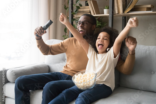 Happy black dad and daughter cheering watching football on TV Canvas Print