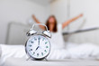 canvas print picture - Closeup alarm clock having a good day with background happy woman stretching in bed after waking up, sunlight in morning. Waking up in the morning on time