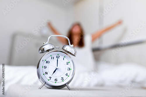 Obraz Closeup alarm clock having a good day with background happy woman stretching in bed after waking up, sunlight in morning. Waking up in the morning on time - fototapety do salonu