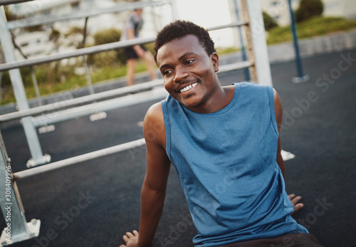 Foto op Plexiglas Ontspanning Cheerful fitness young sportsman resting after training at the outdoor gym park sitting on the ground smiling and looking away