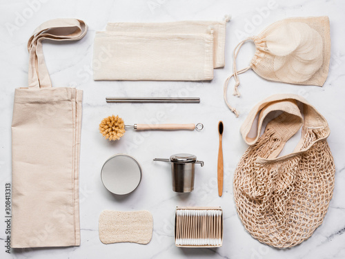 Fotografie, Obraz  Textile eco bags, metal straws and tea infuser, eco-friendly kitchen tools, bamboo toothbrush and cotton buds, reusable cotton pads on white marble background