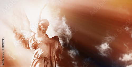 Foto Antique statue of wonderful angel in the rays of the sun on sky background