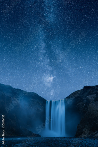 Stampa su Tela  Waterfall at night under a beautiful milky way