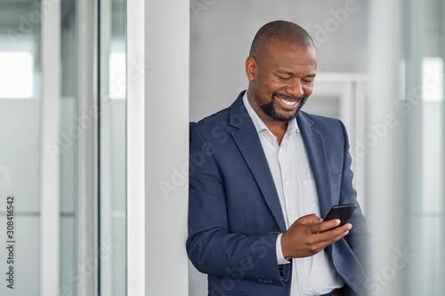 Obraz Mature businessman using smartphone - fototapety do salonu