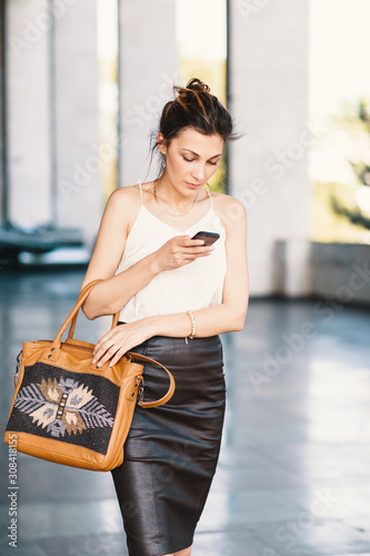 Fototapeta Refined smiling woman walking and writing or reading SMS messages online on a smart phone outdors obraz