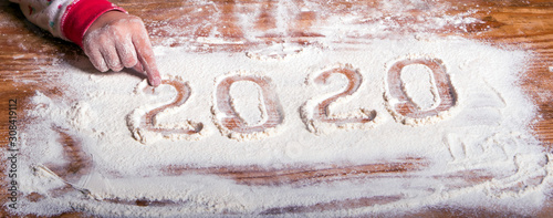 Cuadros en Lienzo  Inscription 2020 with a children's hand on a flour board (New Year background -