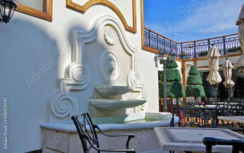Elegant country club patio terrace with outdoor furniture, fountain and sun umbr Wallpaper Mural