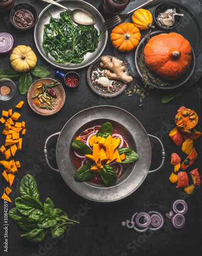Cooking of seasonal vegetarian meals for autumn and winter with pumpkin,spinach, ginger, onion. Top view. Healthy food concept. Fototapete