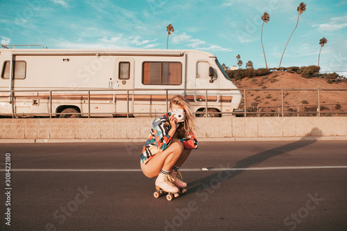 Fototapeta retro style skater girl with a camper van in the background. california lifestyle obraz