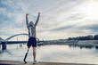 canvas print picture - Highly motivated caucasian handicapped sportsman in sportswear and with artificial leg standing on quay and holding arms up. Only way to win is to be yourself.