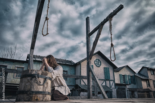 Fotografie, Tablou A woman in medieval dress prays against a cloudy dramatic sky