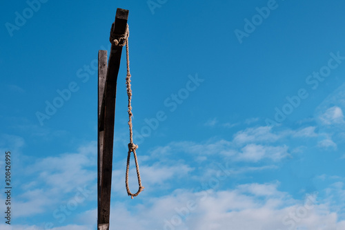 Wooden gallows with old rope and noose against cloudy sky Wallpaper Mural