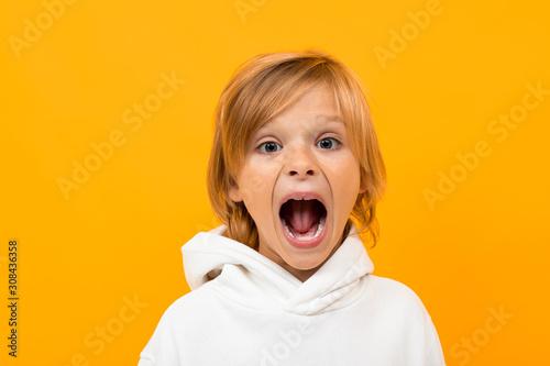 Fototapeta blond boy grimaces on an orange studio background close-up obraz